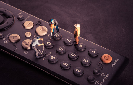 televisor: Miniature worker people fixing on remote control with retro filter