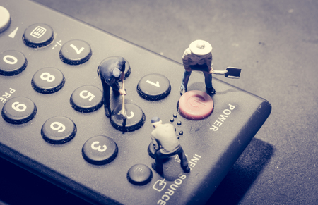 televisor: Miniature worker people fixing on remote with retro filter