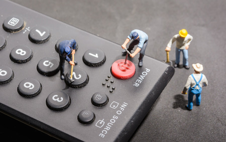 televisor: Miniature worker people fixing on old remote control Stock Photo