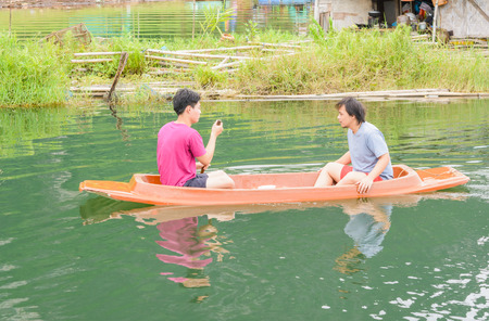 jacked: asia two men driving with kayak on natural forest river
