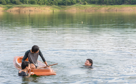 paddles: Kayak capsizing with asia man at natural water river (small boat)
