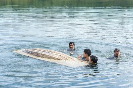 Kayak capsizing with asia man at natural water river (small boat)