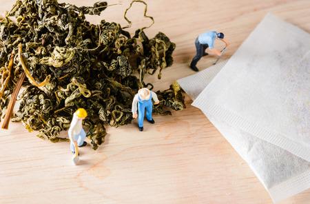 loose leaf: organic loose tea leaf and miniature figure  people working on wood table