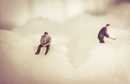 close up Miniature people workers on ice nature. concept snow winter day with vintage filter