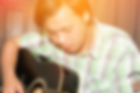 blur background of asia man play acoustic guitar at indoor room. Standard-Bild