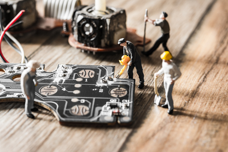 Electronic board with miniature figure worker man at repair and work. Selective focus with vintage filter