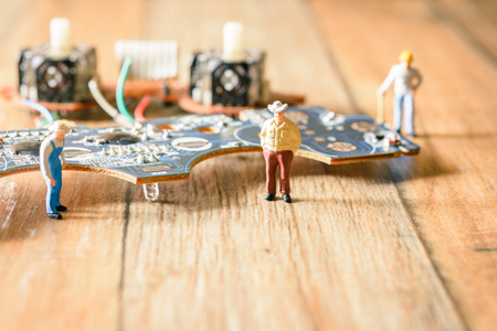 Electronic board with miniature figure worker man at repair and work. Selective focus.(Electronic circuit )