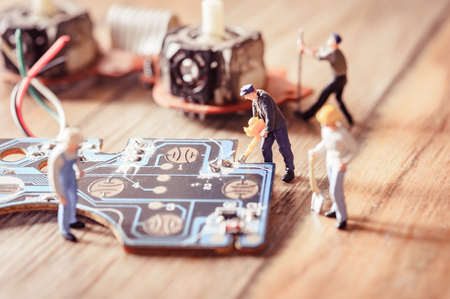 Electronic board with miniature figure worker man at repair and work. Selective focus.(Electronic circuit ) with vintage filter
