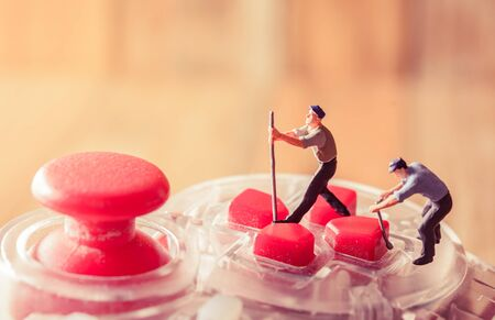 game controller with miniature figure worker man at repair and work. with vintage filter