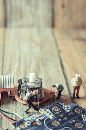 Electronic board with miniature figure worker man at repair and work. Selective focus