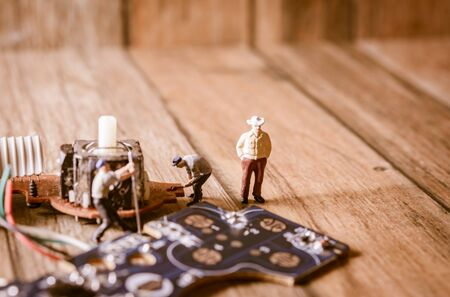 Electronic board with miniature figure worker man at repair and work. with vintage filter