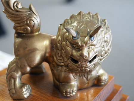 shallow: Ornamental bronze Chinese Lion with shallow depth of field and blurred background