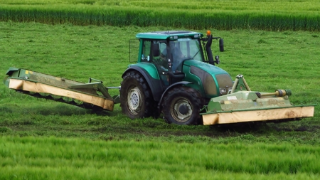 mowing grass: Tractor mowing grass, agricultural labor Stock Photo