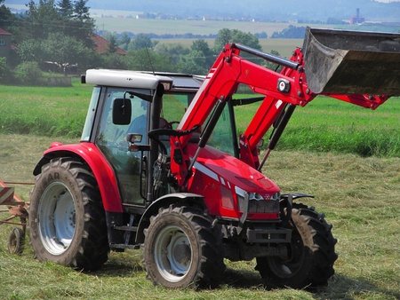 mowing grass: Red tractor mowing grass , agricultural labor Stock Photo