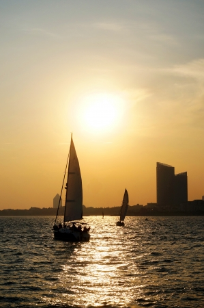 city sunset sailboat seaside at qingdao photo