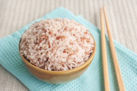 Rice berry, Brown rice and chopsticks in bowl Standard-Bild