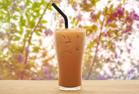 vaso de leche: té helado de leche en la madera con la flor dulce y fondo borroso Foto de archivo