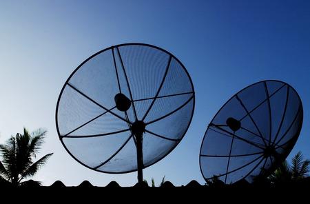 satelite: Silhouette telecommunication satelite dish with blue sky