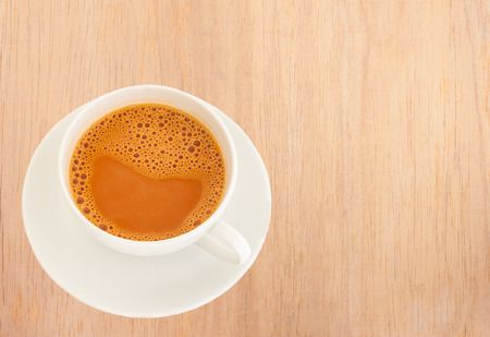 Hot milk tea in a white cup on wooden background