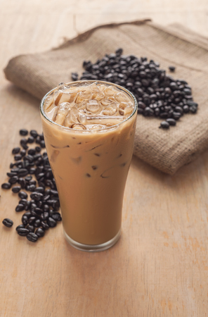 Ice coffee with fresh coffee on a wooden background