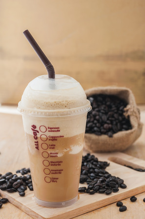 cold background: Ice coffee smoothie with roasted coffee on a wooden background, Still life tone