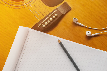 Paper for composer with pencil and headphone on guitar