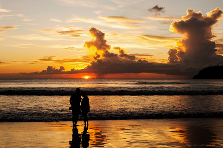 natural love: Emotion of love, Silhouette lovers relax on the beach in color of sunset
