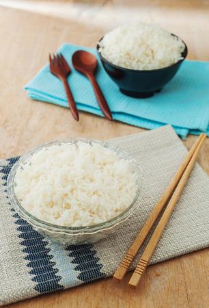 comida japonesa: Arroz blanco en taz�n de fuente negro con los palillos de madera sobre fondo de madera