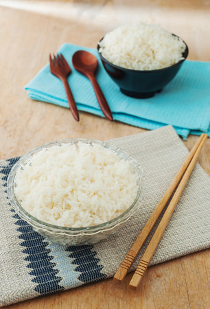 chinese food: White rice in black bowl with wood chopsticks on wooden background