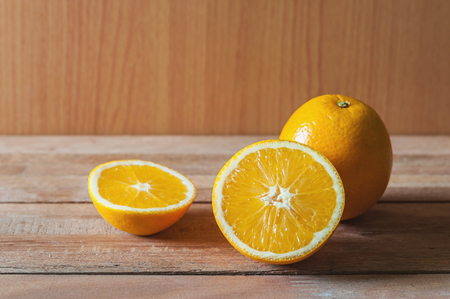 Stil: Orange fruit and slice on wooden table background in still life tone Stock Photo