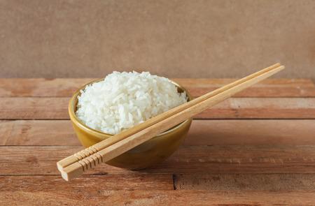 comida japonesa: Arroz blanco en taz�n de caf� con los palillos de madera sobre fondo de madera Foto de archivo