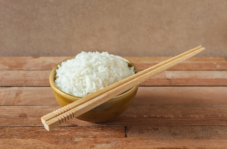 chinese food: White rice in brown bowl with wood chopsticks on wooden background