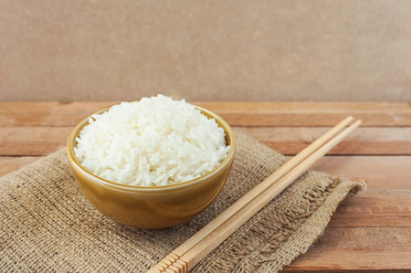 chinesisch essen: White rice in brown bowl with wood chopsticks on wooden background