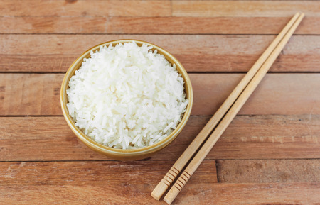 comida japonesa: White rice in brown bowl with wood chopsticks on wooden background
