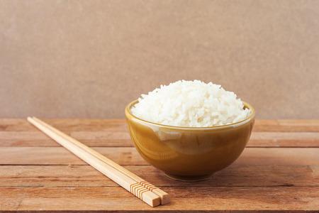 arroz blanco: Arroz blanco en tazón de café con los palillos de madera sobre fondo de madera Foto de archivo