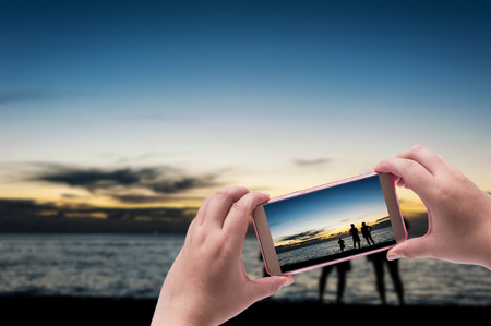 Hand with smart phone shooting photograph on blurred silhouette some people relax and beach sunset in twilight