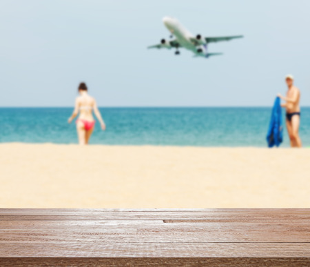plane table: Summer and travel concept, Wood table top on blurred blue sea and white sand beach with some people and plane, Can be used for display or montage your products