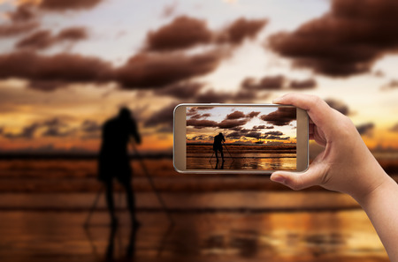 industrail: Hand of women shooting image with smart phone on blurred photographer and beach sunset in twilight