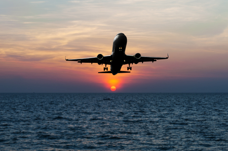 come in: Airplane come down to the land on blurred sea sunset in twilight Stock Photo