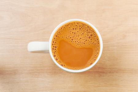 Beber relajarse concepto, té con leche caliente en una taza blanca en la mesa de madera, té del tiempo de relax Foto de archivo - 59040786