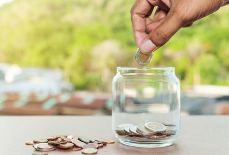 salarios: Cerca de la botella de vidrio con la mano apilando monedas de plata en la mesa de madera, finanzas de las empresas y el concepto de dinero, Ahorre dinero para prepararse en el futuro y el sueño de casa