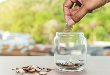 Close up of glass bottle with hand stacking silver coins on wooden table, Business finance and money concept, Save money for prepare in the future and home dream