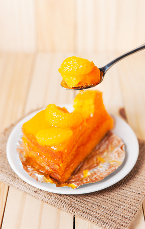 custard slices: Close up orange fruit cake in a stainless spoon on wooden table Stock Photo