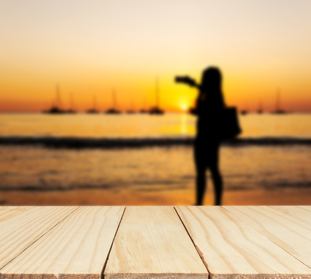 colorful light display: Wood table top on some people and beach sunset colorful in twilight over light the sun, Can be use for display or montage you product