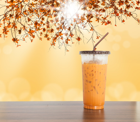 Ice milk tea sweet drink on wooden table with branch and bokeh background
