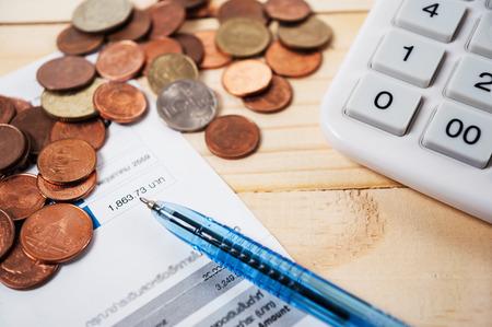 コインとペンとテーブル、収入と支出の夢のために保存のためのお金の計算機との法案