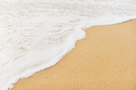 white sand beach: White sand beach and wave of the tropical sea with foam in the day Stock Photo