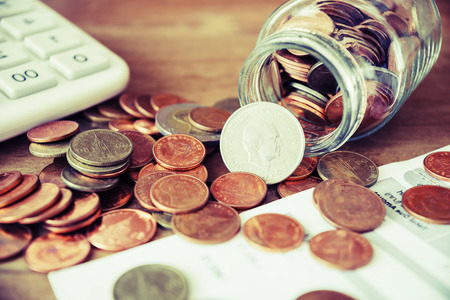 expenditure: Save money for prepare concept, Coins spilling out of a glass bottle with bill and calculator, Bill for income and expenditure vintage style Stock Photo
