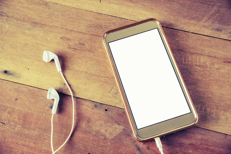 earphone: Smart phone mobile white screen with earphone on wooden table vintage style