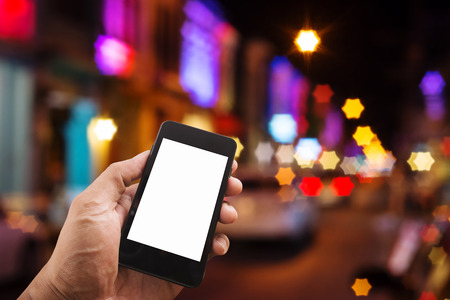 Hand man with smart phone mobile white screen on blurred night city with light bokeh star shape